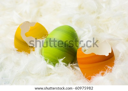 Broken green, orange and yellow easter eggs, hand-painted, lying in white feathers. - stock photo