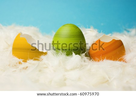 Broken green, orange and yellow easter eggs, hand-painted, lying in white feathers, blue background.