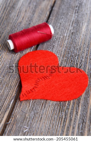 Broken heart and thread on wooden background - stock photo
