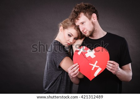 Broken heart difficult love concept. Sad unhappy couple woman and man holding paper red heart fixed with plaster bandage. Rift in relations. - stock photo