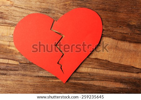 Broken heart on rustic wooden table background - stock photo