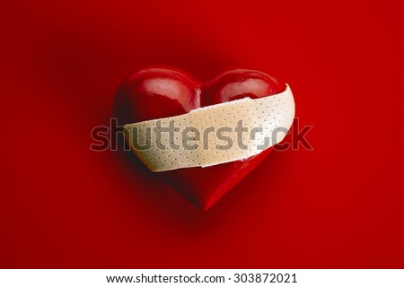Broken heart shape with bandage on white background - stock photo