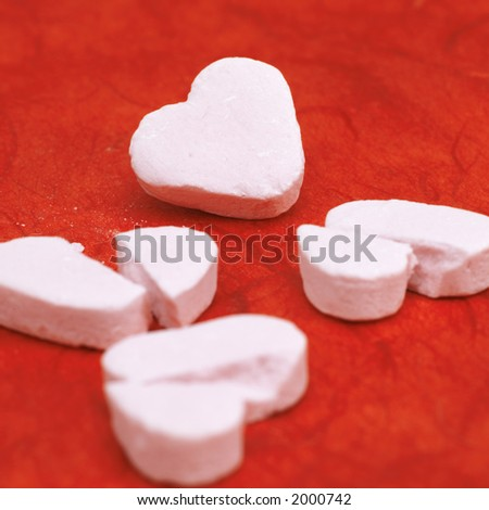 broken hearts  on a red background  (copy space on one of the hearts) - stock photo