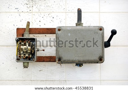 Broken industrial electrical switch and paint stained wall. - stock photo