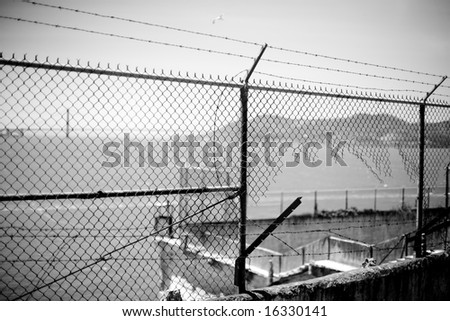 Broken jail yard fence in black and white