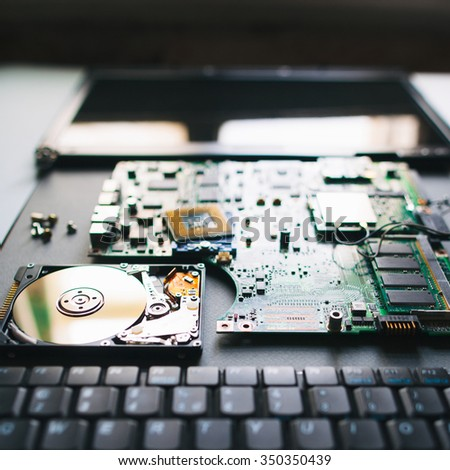 Broken laptop. Electronic components of pc: keyboard, hdd, motherboard (board), cpu (processor), monitor (display) - stock photo