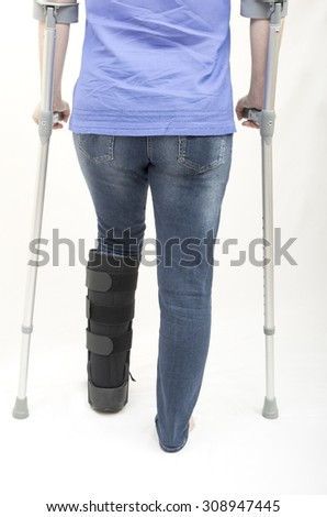 Broken Leg  with Support Boot and Crutches A lady with a fractured leg in an orthopaedic boot walking with the aid of crutches - stock photo