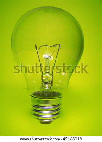 Broken light bulb on green background - stock photo