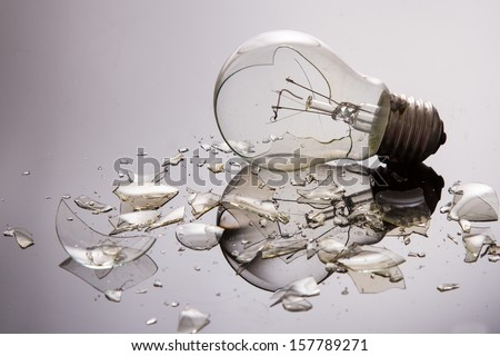 Broken light bulb on shiny surface with pieces backlit - stock photo