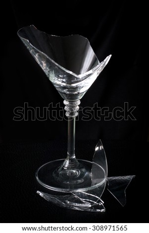 Broken martini glass and debris on a black background - stock photo