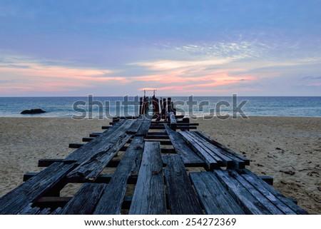 Broken old wooden pier bridge into the sea at Sunset - stock photo