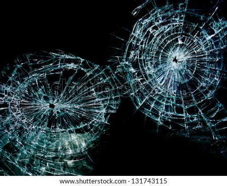 Broken or shattered glass with two holes, on black