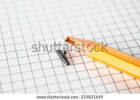 Broken pencil lying on a notepad - stock photo