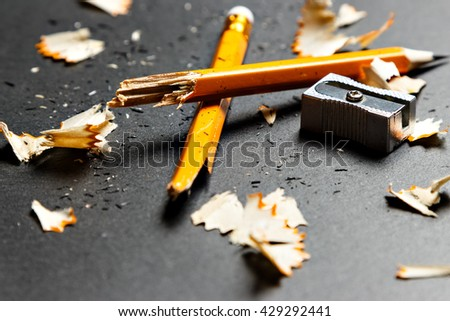 Broken pencil with metal sharpener and shavings on black background. Horizontal image.