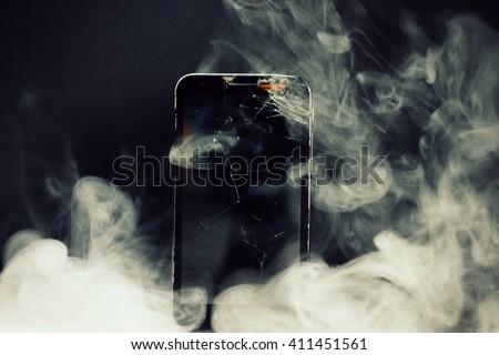 Broken phone and smoke - stock photo