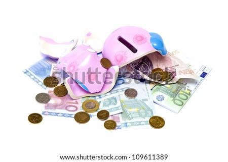 Broken pig money box, coins and banknotes. - stock photo