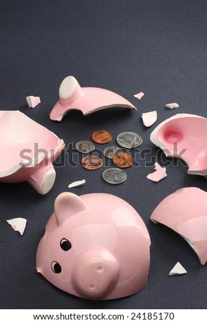 Broken piggy bank containing few coins conveying a sense of misery and financial despair. Copy space available. - stock photo