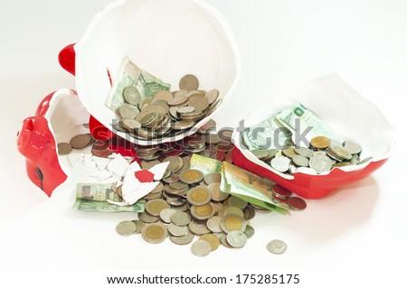 Broken piggy bank with money inside. - stock photo