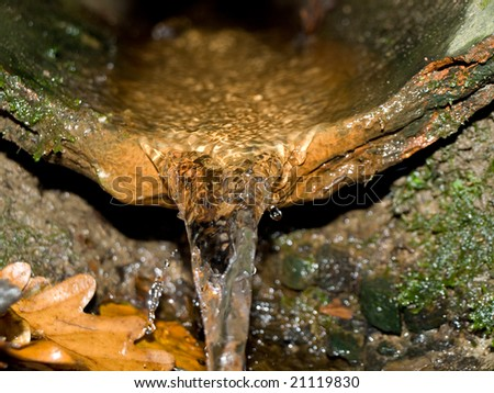 Broken Pipe Underground with Running Water Pouring Out - stock photo