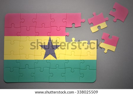 broken puzzle with the national flag of ghana on a gray background - stock photo