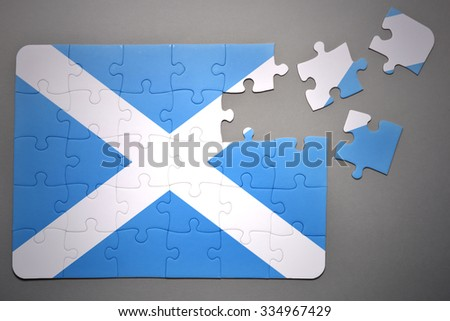 broken puzzle with the national flag of scotland on a gray background - stock photo