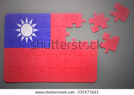 broken puzzle with the national flag of taiwan on a gray background - stock photo