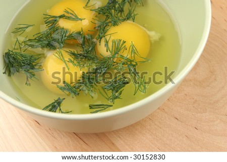 broken raw eggs and fennel inside bowl