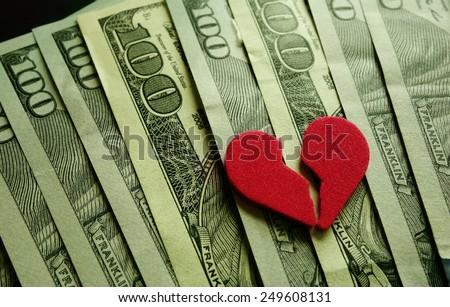 Broken red heart on assorted cash                                - stock photo