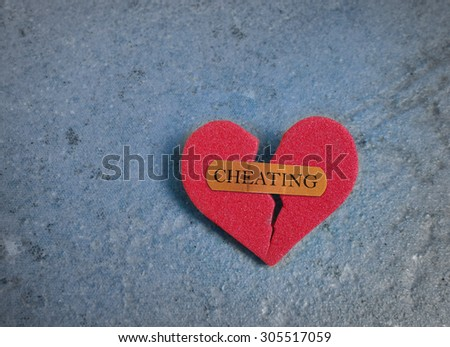 Broken red heart with a bandaid and Cheating text, on blue                                - stock photo