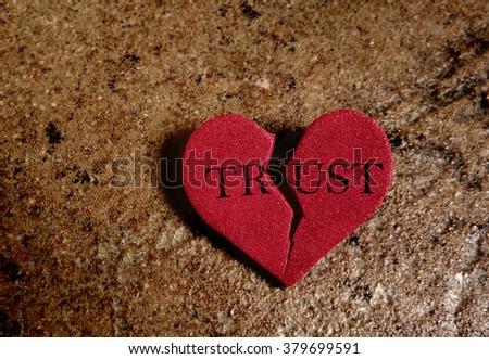 Broken red Trust heart, on textured background                                - stock photo