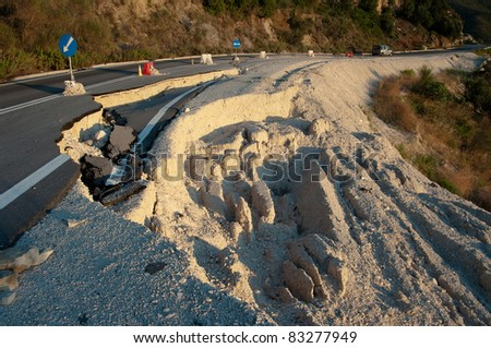 broken road by an earthquake or landslide (road sign) - stock photo