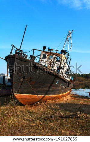broken rusty ship standing on the river bank