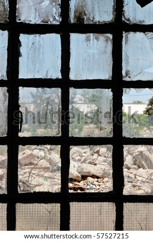 Broken stained window surface of a partially demolished factory. - stock photo