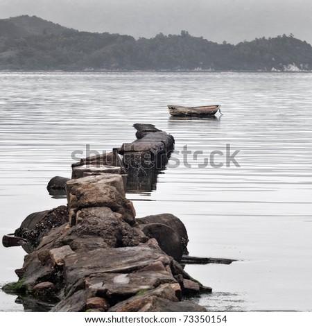 broken stone bridge and boat, low saturation - stock photo
