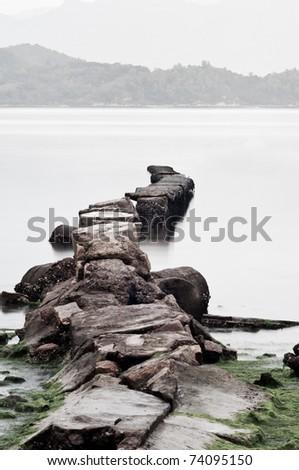 broken stone bridge with long exposure, low saturation - stock photo
