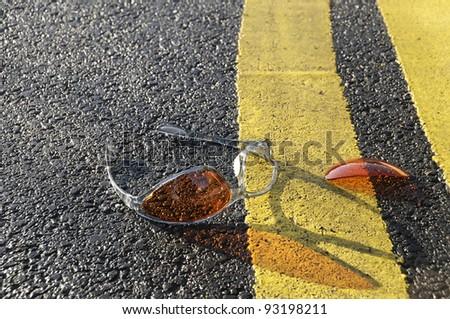 Broken sunglasses found on the road. - stock photo
