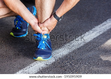 Broken twisted ankle - running sport injury. - stock photo