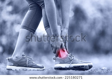 Broken twisted ankle - running sport injury. Female runner touching foot in pain due to sprained ankle. - stock photo