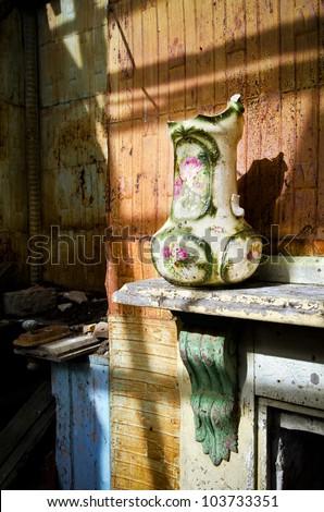 Broken vase on mantle shelf in dilapidated house - stock photo