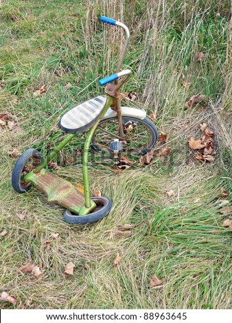 Broken vintage tricycle - stock photo