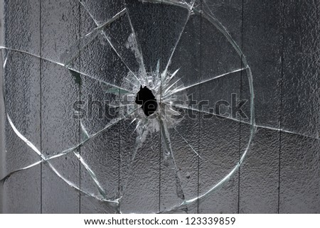 broken window glass with a hole in the middle - stock photo