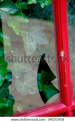 Broken Window in a Red Frame with Ivy - stock photo