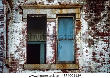 broken window in abandoned expensive brick house