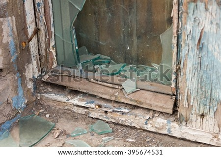 Broken window in an abandoned  building - stock photo