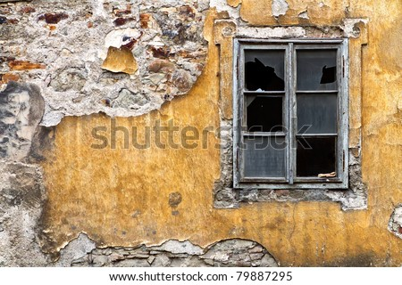 broken window on the yellow  wall - stock photo