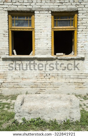 broken windows in a wall of a damaged house - stock photo