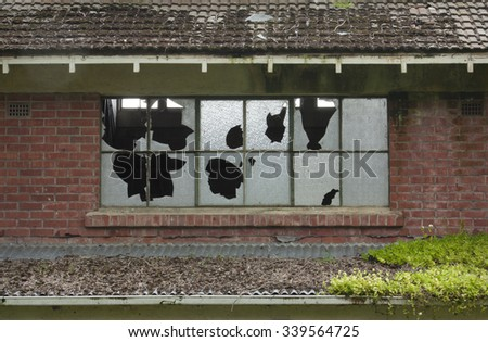 Broken windows in an old abandoned brick building - stock photo