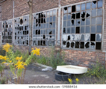 Broken windows in an old industrial building - stock photo