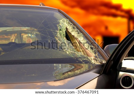 Broken windscreen at black car in traffic accident  - stock photo