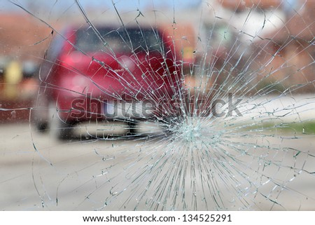Broken windshield with red car in background, selective focus - stock photo
